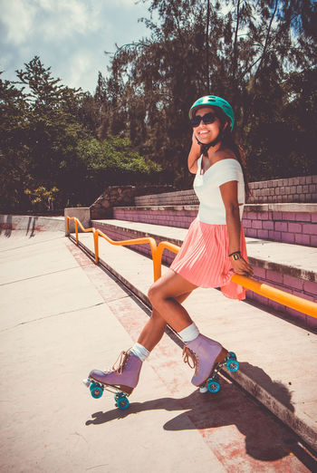 Full length of smiling young woman wearing roller skates