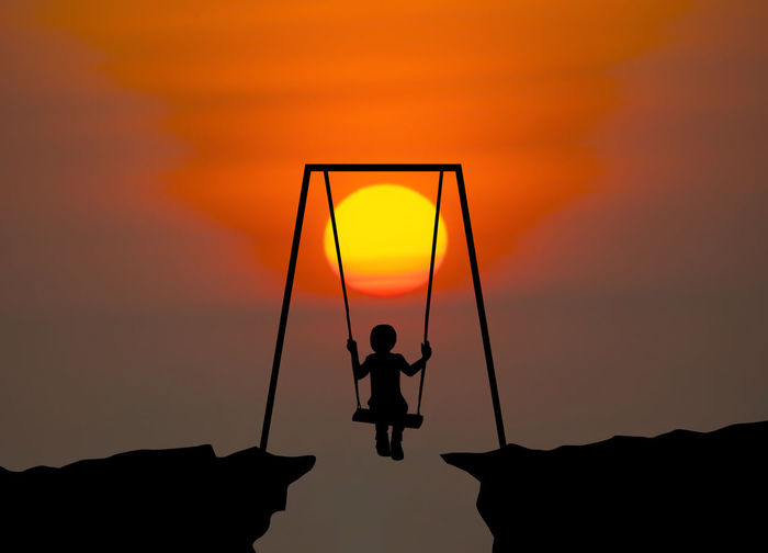 Rear view of silhouette boy on swing against sky during sunset