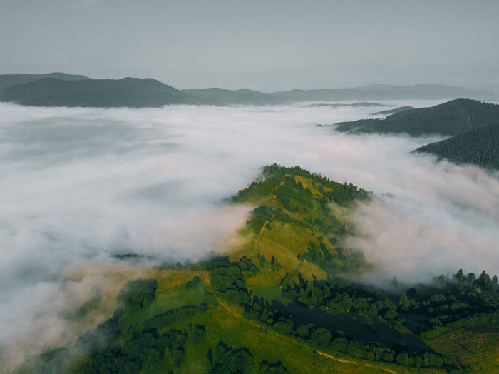 Sea of clouds and picturesque mountains above. beautiful carpathians at early winter or autumn