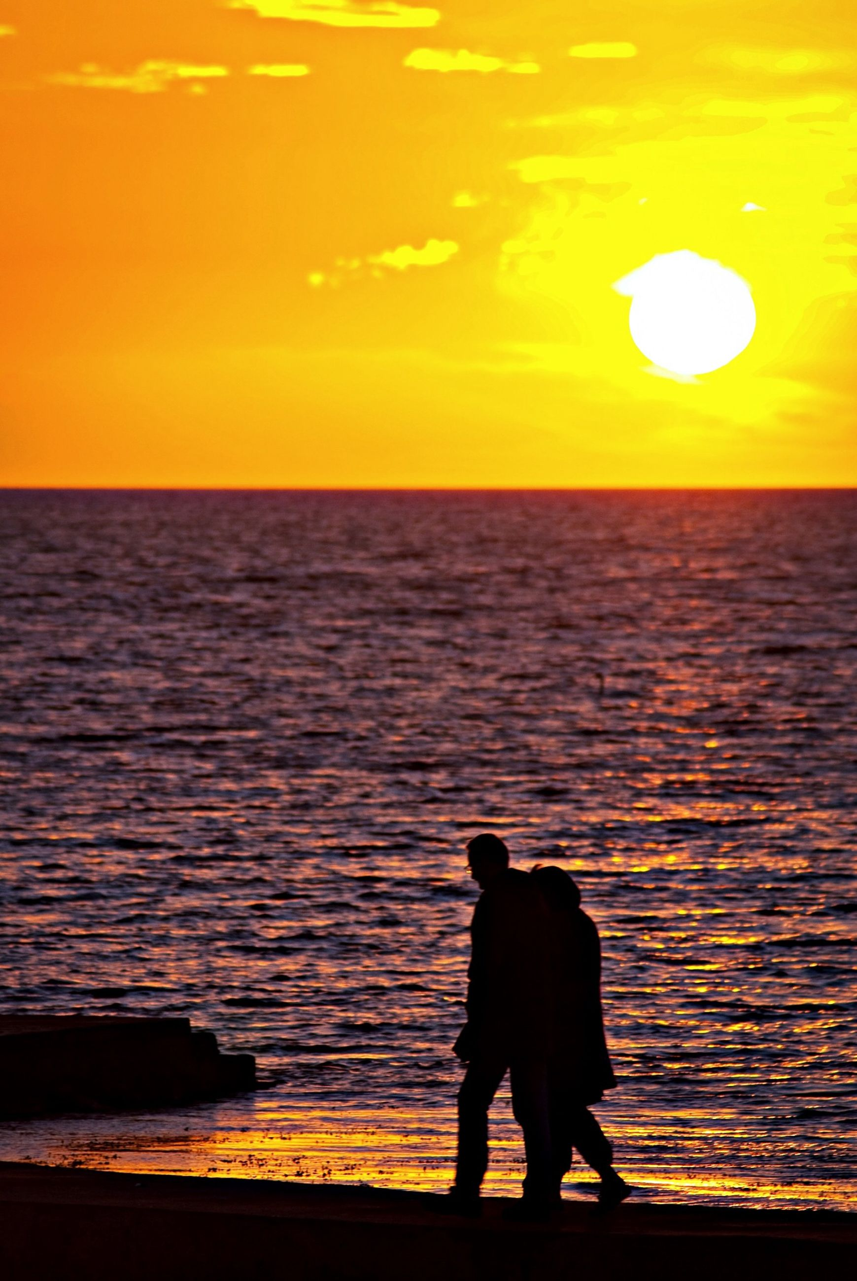 sunset, sea, silhouette, horizon over water, water, orange color, leisure activity, men, scenics, lifestyles, standing, tranquil scene, beauty in nature, sky, tranquility, rear view, sun, nature
