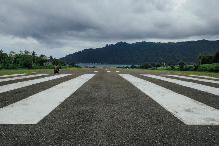 Airfield Airport Asphalt Banda Banda Neira Cloud - Sky Cloudy Country Road Day Empty Empty Road Landscape Mountain Nature Outdoors Road Road Marking Sky Street The Way Forward Transportation Vanishing Point