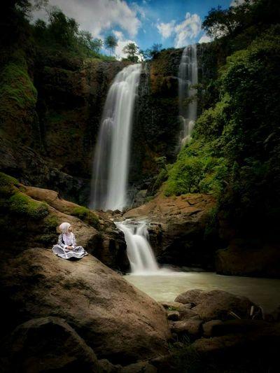 Teenage girl sitting by waterfall