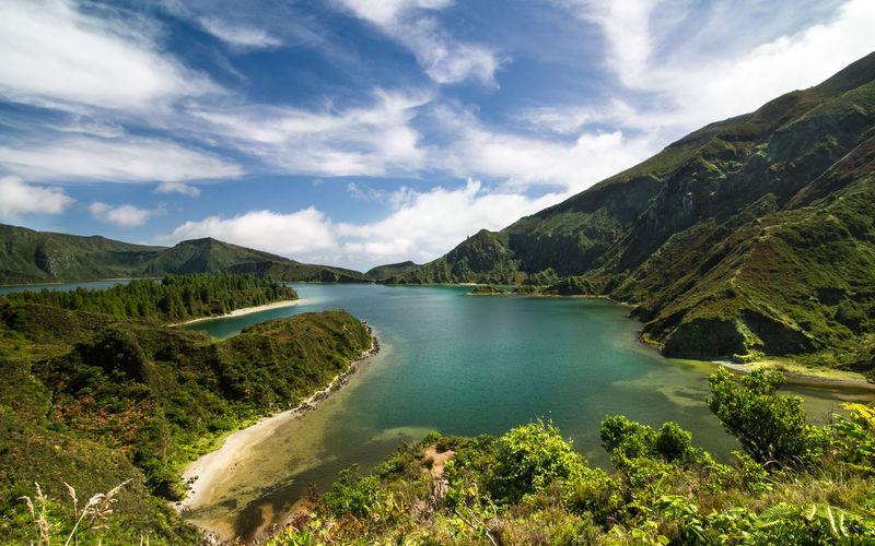 Scenic view of lagoa do fogo amidst mountains against sky