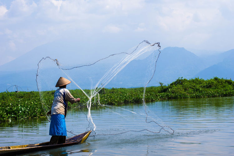 Catch!! Adult Adults Only Catch Of Fish Day Fisherman Fishing Fishing Net Fishing Tackle Humaninterestindonesia Lake Motion Nature One Man Only One Person Outdoors People Rawapening #indonesia #centraljava Sky Water