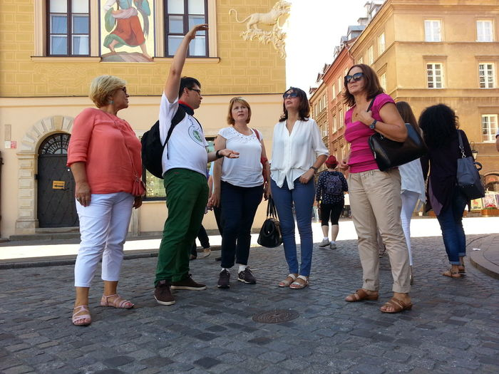A few people listening to the tour guide Bosses Meeting Capital City Grouo100 Guide Interesting Natural Sunny Weather Tour Guide Warsaw Old Town