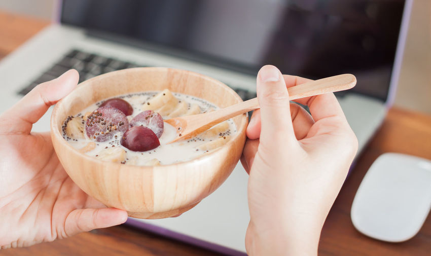 Close-up of hand holding bowl of milk and plum with chopped banana