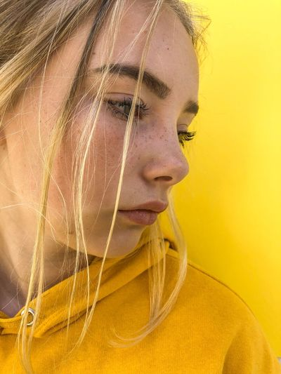 Close-Up Of Teenage Girl With Blond Hair Against Yellow Background