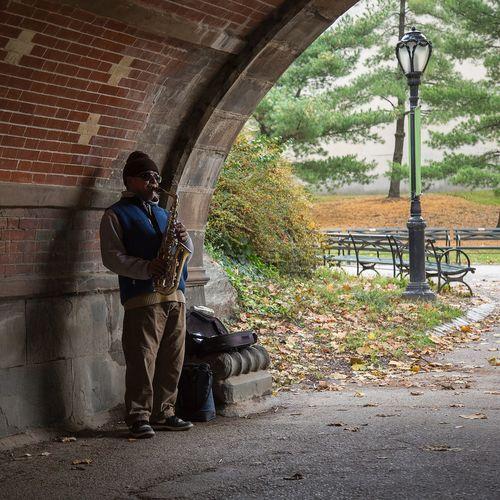 Full length of man sitting on street against wall