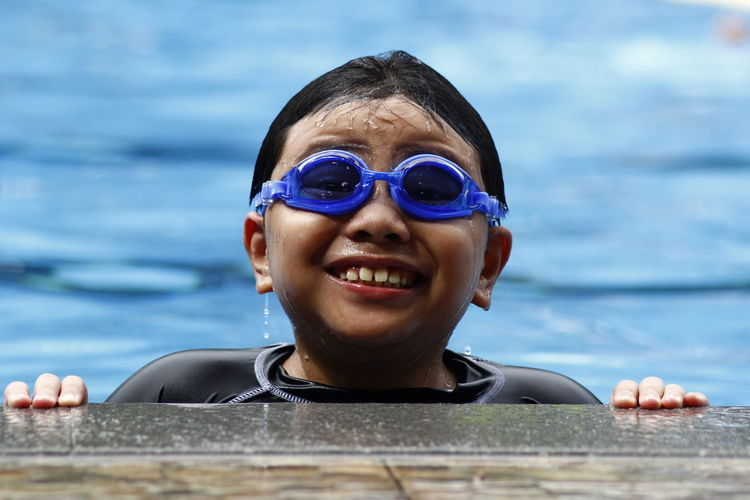 Portrait of smiling boy wearing swimming goggles in pool