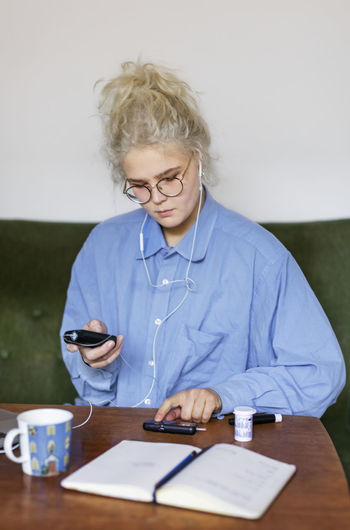 Mid adult woman using smart phone on table