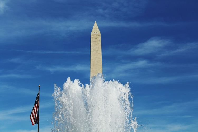Fountain in front of washington monument against sky