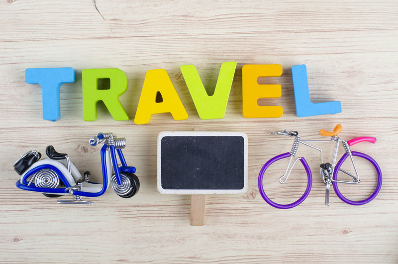 top view vacation and holiday concept word TRAVEL with accessories on wooden background Text Western Script Indoors  Wood - Material Still Life Multi Colored Table Directly Above Capital Letter Communication No People High Angle View Letter Toy Alphabet Variation Blue Education Choice Wood Grain