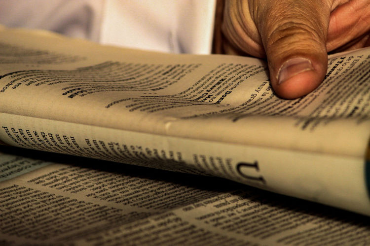 Close-up of cropped hand holding newspaper