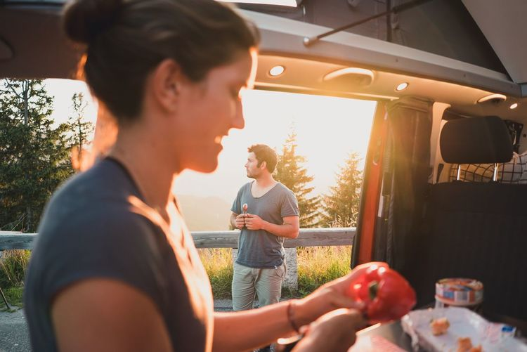 Couple camping in sunset Mood Life Live Authentic Road Trip Sunset Cooking Camping Two People Young Adult Food And Drink Young Women Young Men Food Real People Casual Clothing Lifestyles Togetherness Young Couple Healthy Eating Leisure Activity Fruit Standing Day Drink Smiling Friendship Men