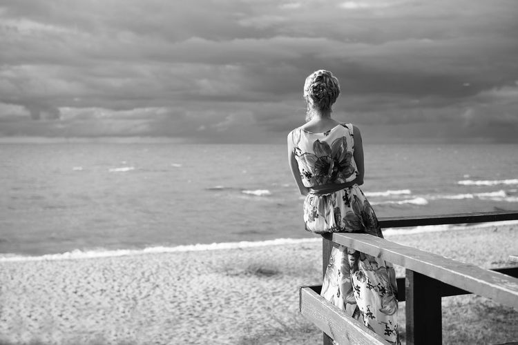 Rear view of woman sitting on railing at beach against cloudy sky