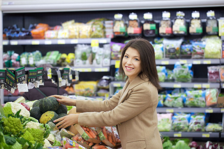Portrait Of Happy Woman Buying Vegetables In Store