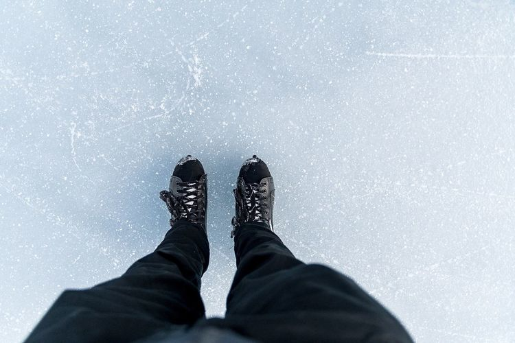 Low section of man standing on ice rink during winter
