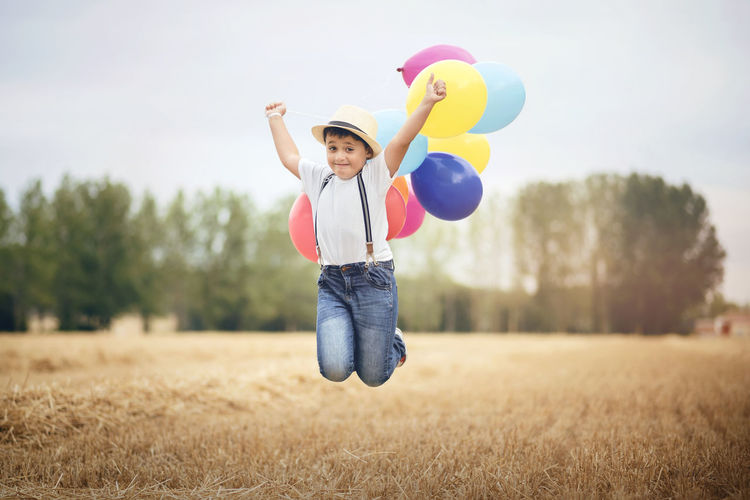 Freedom Fun Happiness Happy Holidays Independence Jump Lifestyle Sunlight Adventure Balloon Boy Child Childhood Field Joy Jumping Playful Playing Sky Smile Smiling Straw Summer