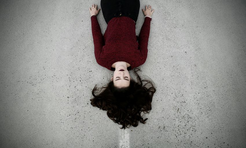 High angle view of beautiful woman lying on road