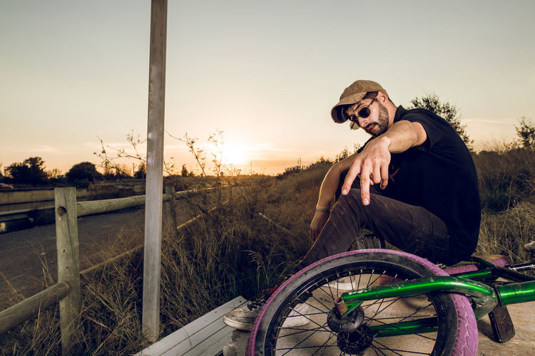 Man looking at bicycle against sky during sunset