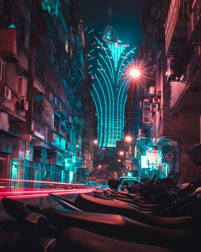Cars on illuminated street amidst buildings at night