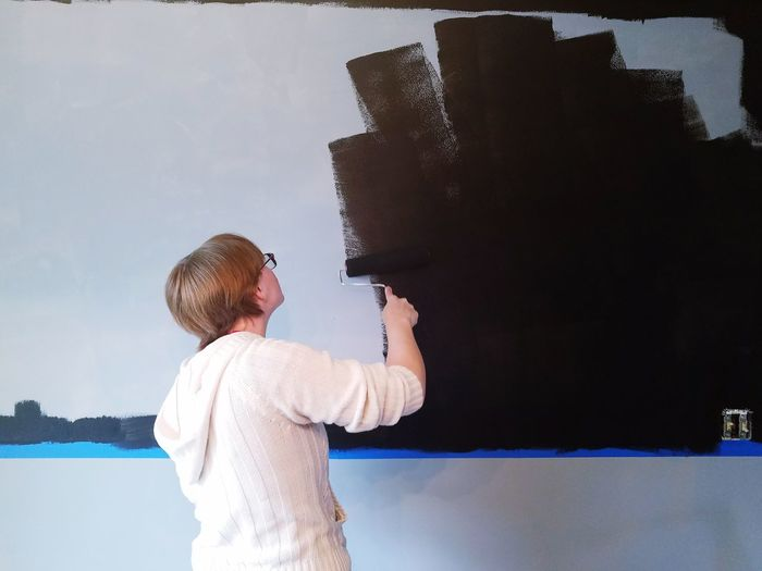 Rear view of young woman painting wall