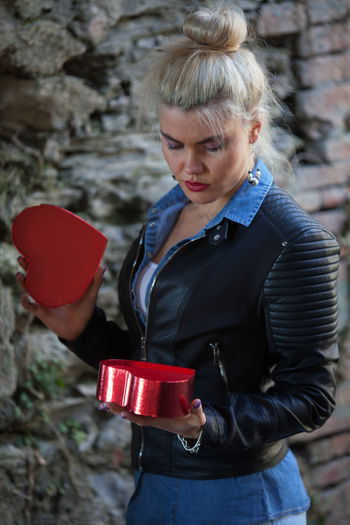 Young woman holding red heart shaped container