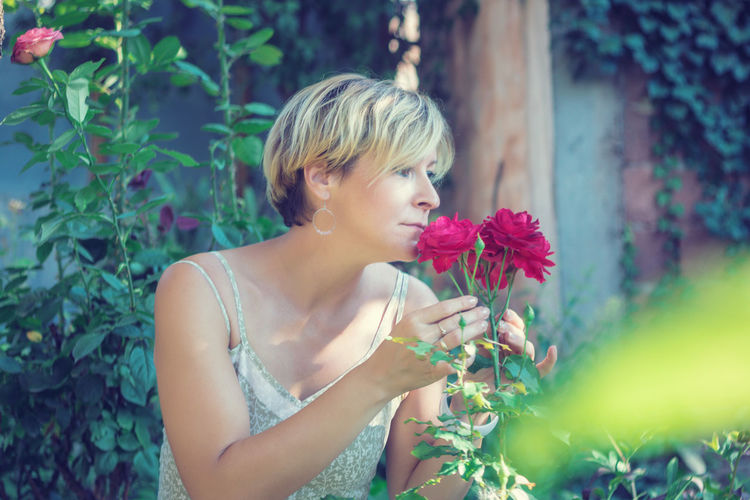 Beautiful woman holding red flowering plant