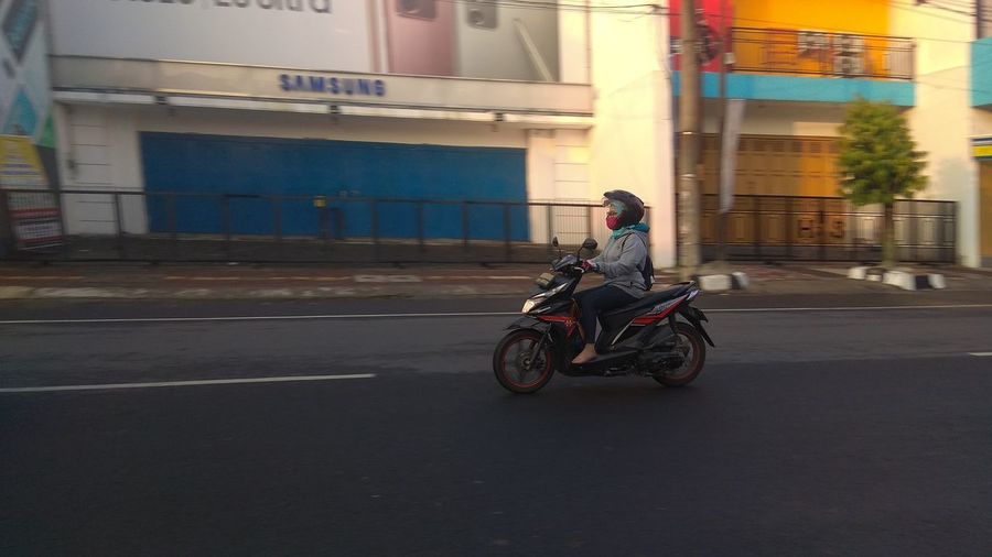 Side view of man riding motorcycle on road