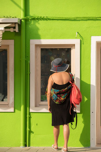 A Day in Burano Architecture Building Exterior Casual Clothing Day Full Length Green Color Looking In The Shop Window One Person Rear View Standing Travel Destinations Travel Photography Vivid Lime Green House Woman In Hat Women