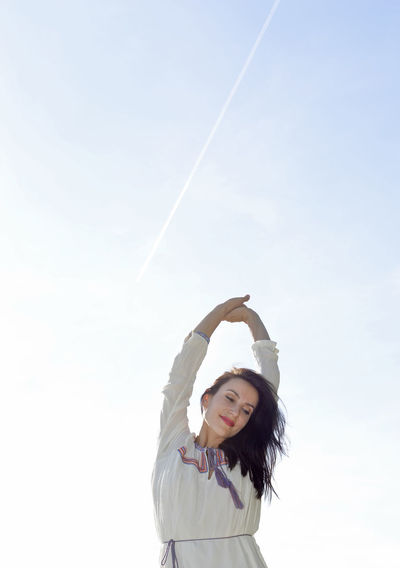 Smiling Woman With Arms Raised Standing Against Clear Sky