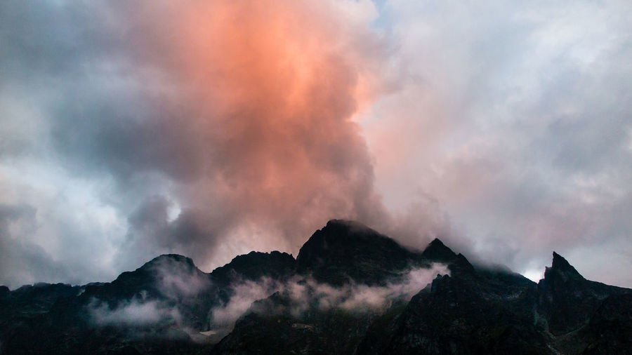 Low angle view of mountains against cloudy sky at sunset
