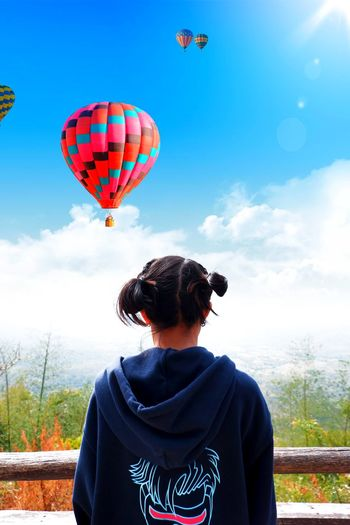 Rear view of man looking at balloons against sky