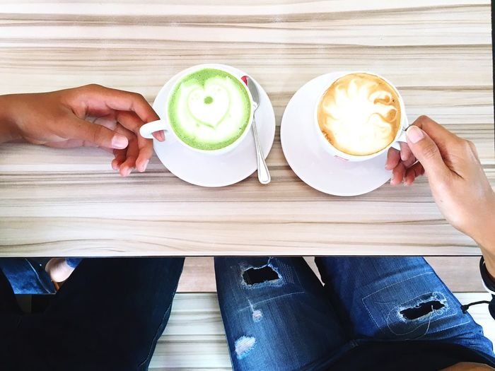 Cropped image of people having coffee at table