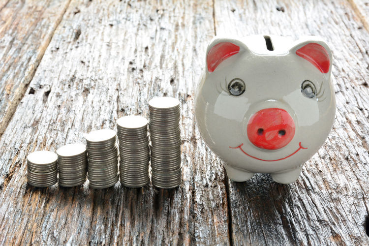 High Angle View Of Coins With Piggy Bank On Wooden Table