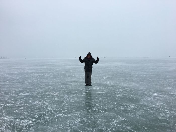 Man standing on frozen sea against sky
