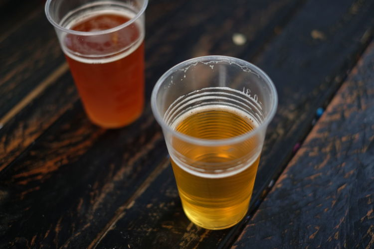 Beer in disposable glasses on wooden table