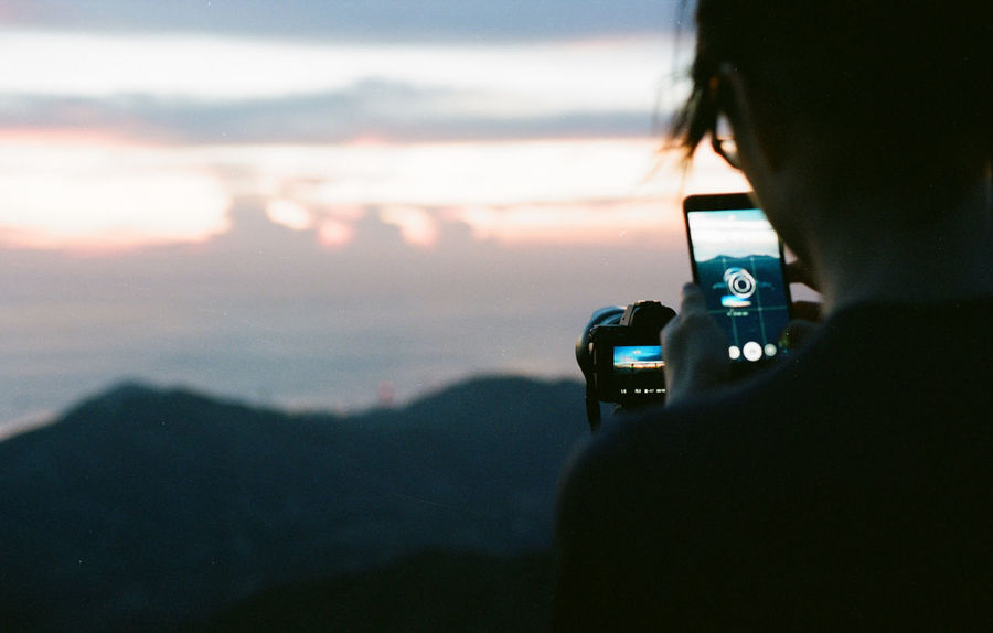 Taking photo of photo Adult Beauty In Nature Camera - Photographic Equipment Close-up Day Digital Camera Holding Landscape Mobile Conversations Mountain Nature One Person Outdoors People Photographer Photographing Photography Themes Real People Rear View Scenics Sky Sunset Technology