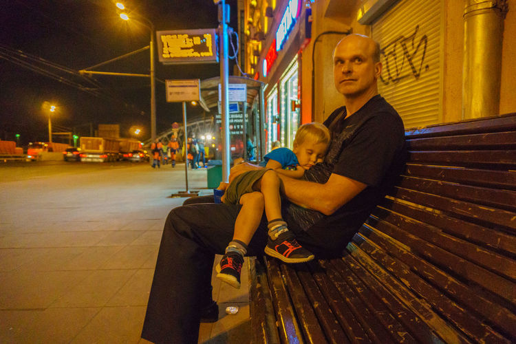 Father with son sleeping on lap at bench during night