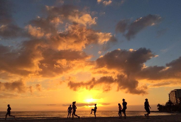 Group of silhouette people running on beach at sunset