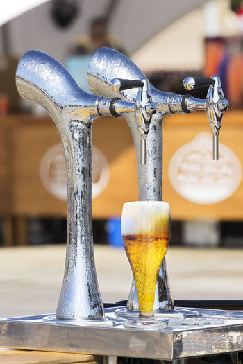 Close-up of glass under beer tap
