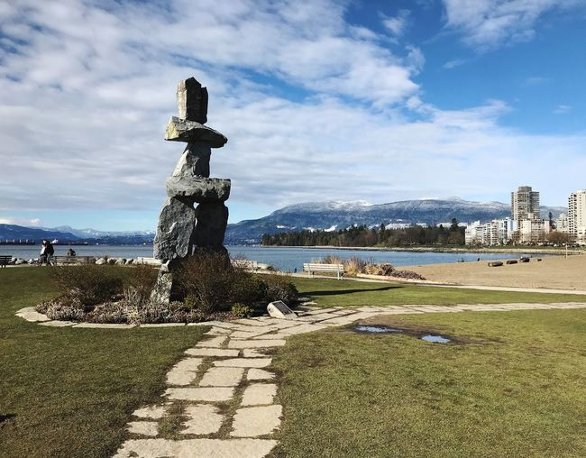 Inukshuk at English Bay West Coast First Nations Inuksuk Inukshuk Beach Vancouver Canada Sky Cloud - Sky Nature Day Sunlight No People Plant Architecture Water Land Built Structure Grass Art And Craft Outdoors Human Representation Stone Tranquility Sculpture