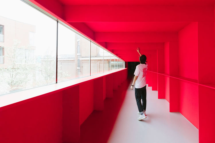 Red Dimension Bright Exploring EyeEm Best Shots Adult Architectural Column Architecture Bold Building Built Structure Casual Clothing Day Full Length Indoors  Lifestyles Minimalism One Person Reaching Out Real People Rear View Red Standing Women