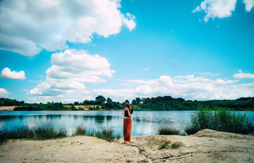 Adult Beauty In Nature Cloud - Sky Day Full Length Lake Leica Leisure Activity Looking At Camera Nature One Person Outdoors People Portrait Real People Rear View Scenics Sky Standing Tranquil Scene Tree Water Women Young Adult Young Women