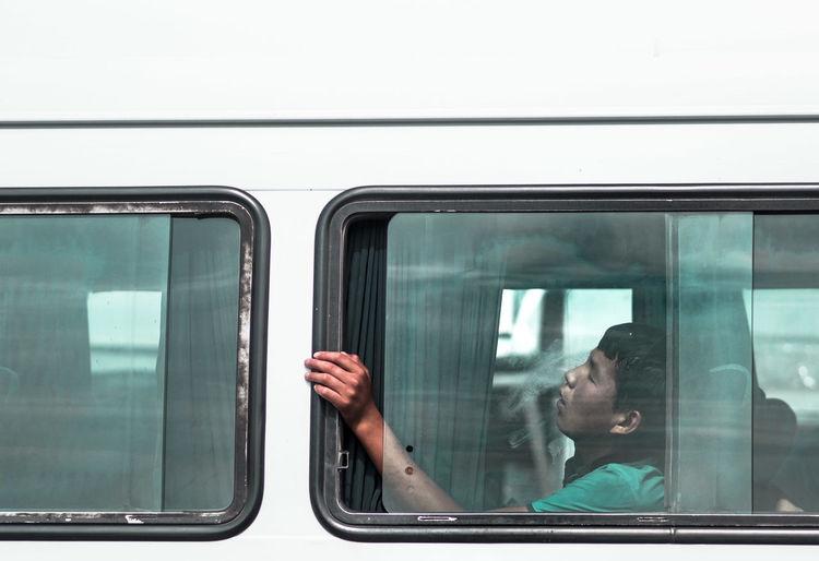 Portrait of man looking through train window