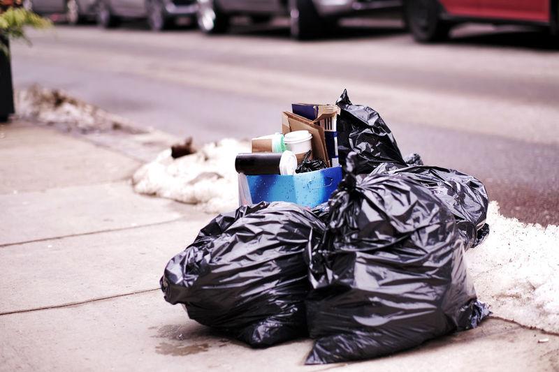 Garbage bin on sidewalk in city