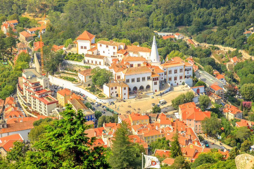Aerial view of ancient wall and tower of Castle of the Moors and Sintra valley. Castelo dos Mouros is medieval castle and Unesco Heritage on a hill above Sintra, Lisbon District, Portugal. Pena Palace and the ruins of Moors Castle are popular landmarks and major tourist attractions of the Cultural Landscape of Sintra as a World Heritage Site, Portugal. Portugal Sintra Castle Ruins Medioeval Cities Wall Tourism Flags Skyline Cityscape Palace Castle Ruin Aerial View Moors Castle Pena Palace Moors Architecture Building Exterior Built Structure Tree Building Plant Residential District City Day High Angle View No People Nature House Town Travel Destinations Roof Outdoors Community Green Color History TOWNSCAPE