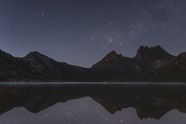 Scenic View Of Calm Lake And Mountains Against Sky At Night