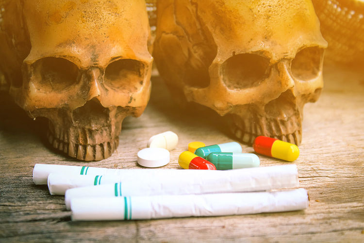 Close-Up Of Pills And Cigarettes With Human Skull On Table