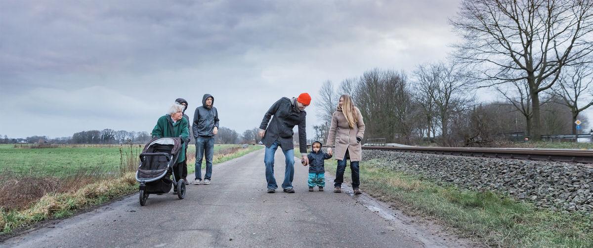 Full length of family walking on road against sky